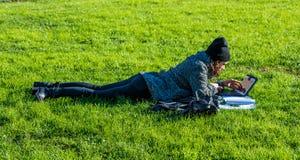 Muchacha con la tableta, mintiendo en hierba verde y la escritura Foto de archivo libre de regalías