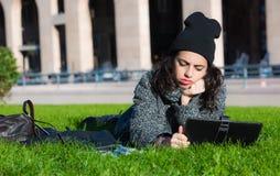 Muchacha con la tableta, mintiendo en la hierba verde que parece agujereada Fotografía de archivo libre de regalías