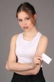 Muchacha con la tarjeta blanca en su mano Cierre para arriba Fondo gris Foto de archivo libre de regalías