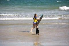 Muchacha con la tarjeta de la boogie en la playa Fotografía de archivo libre de regalías