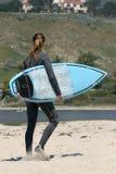 Muchacha con la tarjeta que practica surf Imagen de archivo libre de regalías