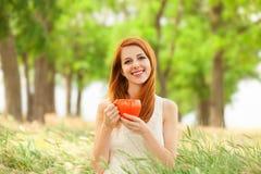 Muchacha con la taza anaranjada Imagen de archivo libre de regalías