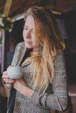 Muchacha con la taza blanca en el mirador de la casa té de consumición de la muchacha, mujer con una taza de café Foto de archivo