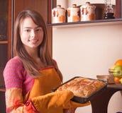 muchacha con la torta en cocina Foto de archivo libre de regalías