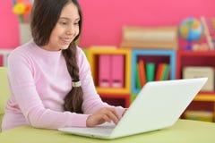 Muchacha con la trenza usando el ordenador portátil Fotografía de archivo libre de regalías