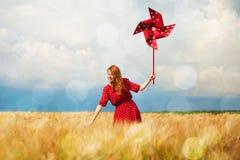 Muchacha con la turbina de viento del juguete imagen de archivo libre de regalías