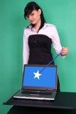Muchacha con la varita y la computadora portátil mágicas con la pantalla en blanco. Foto de archivo