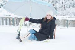 Muchacha con las aletas que se sientan en nieve Fotografía de archivo