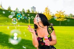 Muchacha con las burbujas jabonosas Imagenes de archivo