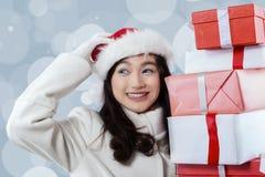Muchacha con las cajas del sombrero y de regalo de santa Foto de archivo