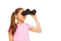 Muchacha con las colas de caballo con los prismáticos Fotografía de archivo