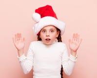 Muchacha con las coletas en el sombrero de Santa Claus Fotografía de archivo