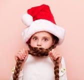 Muchacha con las coletas en el sombrero de Santa Claus Foto de archivo