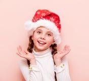 Muchacha con las coletas en el sombrero de Santa Claus fotografía de archivo libre de regalías