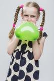 Muchacha con las coletas que presentan en la polca Dot Dress Against White Explotar el balón de aire en forma de corazón verde Imagen de archivo