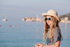 muchacha con las estrellas de mar que se colocan en la playa Imágenes de archivo libres de regalías