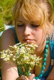 Muchacha con las flores de la manzanilla Imagenes de archivo