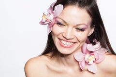 Muchacha con las flores de la orquídea en pelo Imagen de archivo