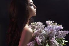 Muchacha con las flores detrás de la ventana mojada Imagen de archivo libre de regalías