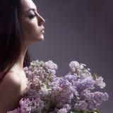 Muchacha con las flores detrás de la ventana mojada Fotos de archivo