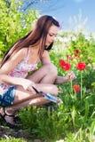 Muchacha con las flores en jardín Foto de archivo libre de regalías