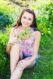 Muchacha con las flores en jardín Fotos de archivo libres de regalías