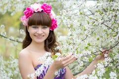 Muchacha con las flores en la cabeza y el árbol floreciente Foto de archivo