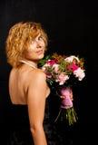 Muchacha con las flores que miran al revés Imagenes de archivo