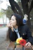 Muchacha con las flores que ponen en el banco en parque Imagen de archivo