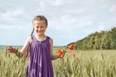Muchacha con las flores rojas que presentan en el campo de trigo, sol brillante, paisaje hermoso del tulip?n del verano imagenes de archivo