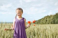 Muchacha con las flores rojas que presentan en el campo de trigo, sol brillante, paisaje hermoso del tulip?n del verano foto de archivo
