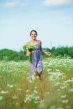 Muchacha con las flores salvajes de la primavera Fotografía de archivo libre de regalías