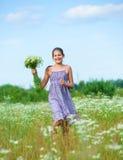 Muchacha con las flores salvajes de la primavera Fotografía de archivo