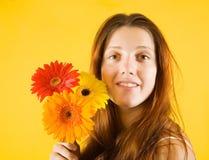 Muchacha con las flores sobre amarillo Foto de archivo libre de regalías