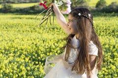 Muchacha con las flores y el vestido de la comunión Foto de archivo libre de regalías