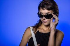 Muchacha con las gafas de sol en fondo azul Imagen de archivo