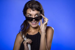 Muchacha con las gafas de sol en fondo azul Fotos de archivo