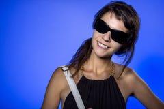 Muchacha con las gafas de sol en fondo azul Foto de archivo