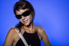 Muchacha con las gafas de sol en fondo azul Imágenes de archivo libres de regalías