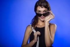 Muchacha con las gafas de sol en fondo azul Foto de archivo libre de regalías