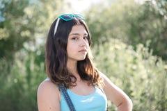 Muchacha con las gafas de sol en su cabeza que presenta en naturaleza Fotos de archivo