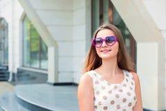 Muchacha con las gafas de sol púrpuras en forma de corazón que miran para arriba para echar a un lado para copiar el sueño del es imagen de archivo libre de regalías