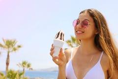 Muchacha con las gafas de sol que come el helado en la playa de Tenerife con las palmeras en el fondo foto de archivo