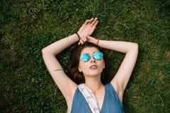 Muchacha con las gafas de sol que mienten en la hierba en día de verano en parque de la ciudad Fotografía de archivo libre de regalías