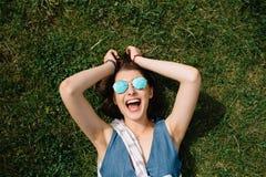 Muchacha con las gafas de sol que mienten en la hierba en día de verano en parque de la ciudad Imágenes de archivo libres de regalías