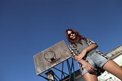Muchacha con las gafas de sol que miran abajo detrás con viejo baloncesto Fotos de archivo libres de regalías