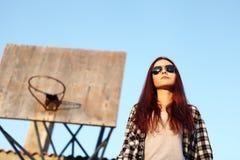 Muchacha con las gafas de sol que miran el cielo detrás del aro de baloncesto Fotografía de archivo