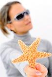 Muchacha con las gafas de sol y las estrellas de mar Fotografía de archivo