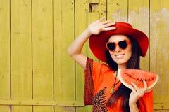 Muchacha con las gafas de sol y Red Hat con la rebanada de la sandía foto de archivo