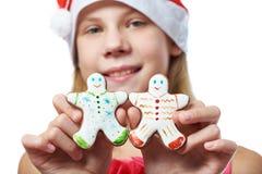 Muchacha con las galletas del hombre de pan de jengibre de la Navidad en manos Fotografía de archivo
